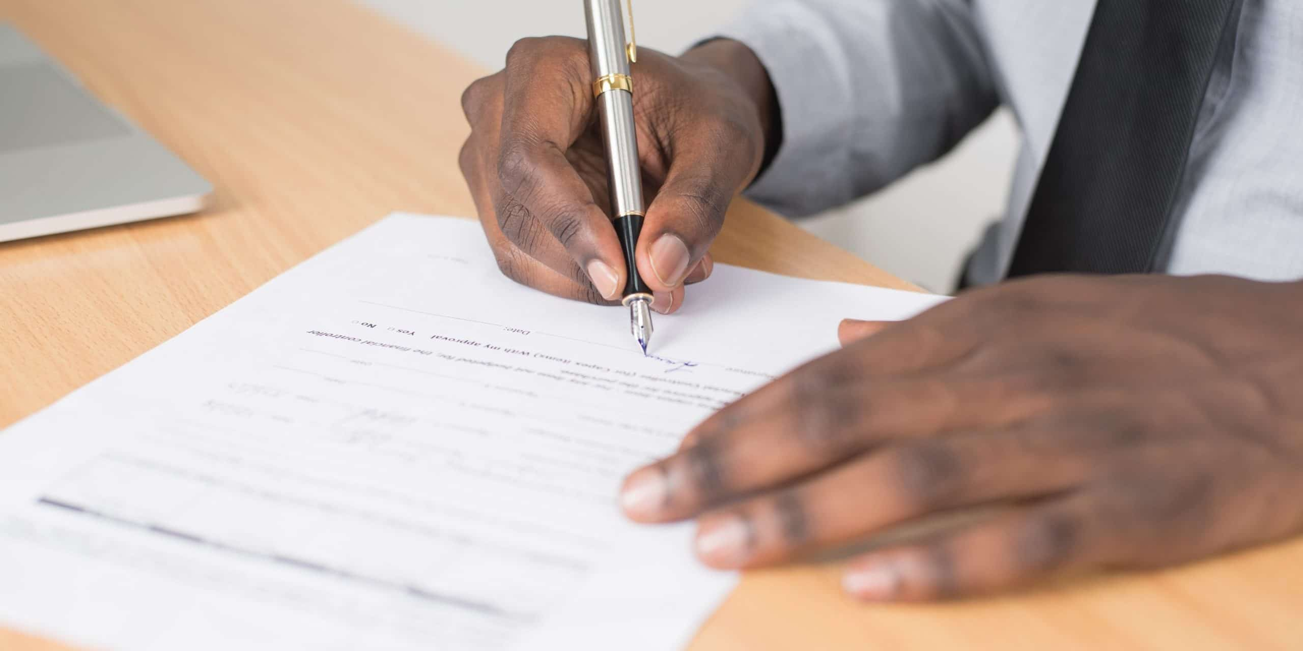 Close up view of person's hands filing out a form on a desk