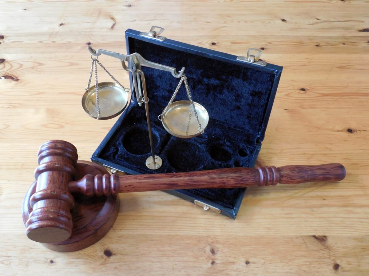 gavel on a desk next to small justice scales