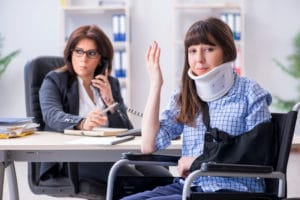 Woman with long brown hair and neck brace and sling frustrated as she talks with a Workers' Comp insurance adjuster