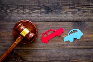 Judge's gavel and red and blue paper cutout cars on a wooden surface